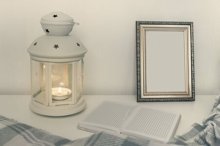 Winter still life interior details, lantern with burning candle, open book and a photo frame on the table.