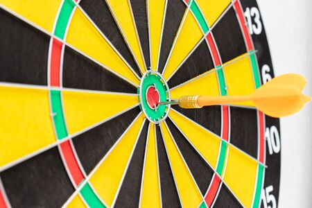 A dart board with an arrow in bullseye close up, goals and targetting concept.