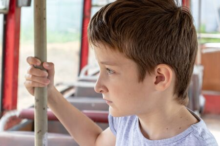 A 10 years boy riding in a old vintage bus, he is sad because his poor life and the bus moving going on a dirty country road. Reklamní fotografie - 141531680
