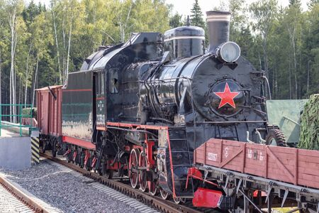 Moscow, Russia - July 28, 2019: An old black Soviet steam locomotive with a red star on the hull stands on the platform of the station in Patriot Park in summer. Reklamní fotografie - 141900887