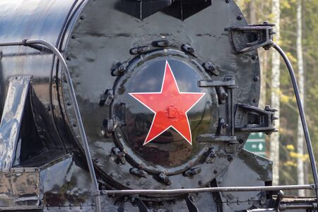 Moscow, Russia - July 28, 2019: An old black Soviet steam locomotive with a red star on the hull stands on the platform of the station in Patriot Park in summer.