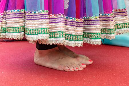 Female feet in a sari standing on a red carpet during wedding ceremony.
