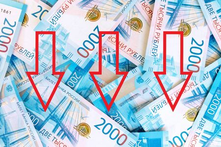 Background of paper russian money, banknotes of 2000 two thousands rubles with red down arrows as a symbol of devaluation russian currency. Reklamní fotografie - 141246022
