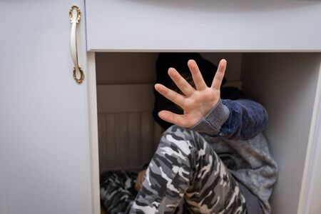 A teenage boy sitting under the table and hiding his face with a hand.