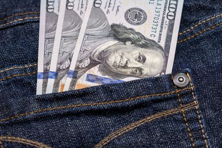 American us one hundred dollar banknotes in a jeans pocket.
