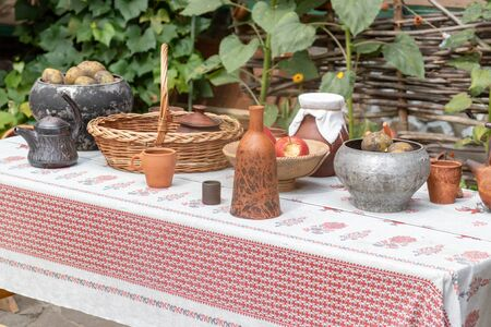 Traditional outdoor ukrainian festive table setting in rustic style for wedding ceremony with clay tableware and decorative tablecloth in summer, wattle and wooden house on background. Reklamní fotografie