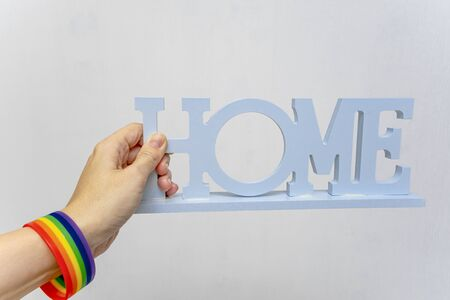 Hand wearing Lgbt rainbow gay pride bracelet holding a sign home on white background. Reklamní fotografie - 141989158