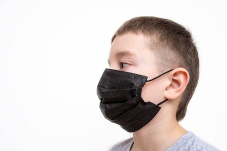 A portrait of a boy wearing surgical medical black face mask on white background. Reklamní fotografie - 141989160