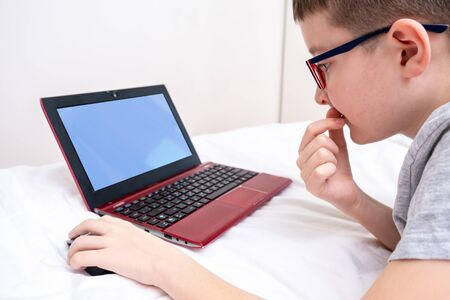A preteen boy lying on a bed, surfing internet and typing into his blog, child blogging concept. Reklamní fotografie - 141989162