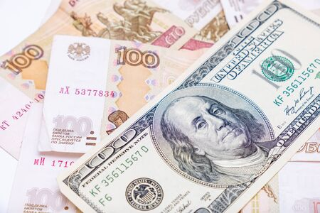 Us dollars banknotes lying over russian rubles background, financial crisis and choosing currency for savings, ruble devaluation concept.