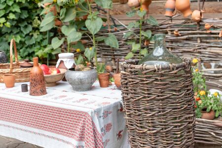 Traditional outdoor ukrainian festive table setting in rustic style for wedding ceremony with clay tableware and decorative tablecloth in summer, wattle and wooden house on background. Reklamní fotografie - 141989188