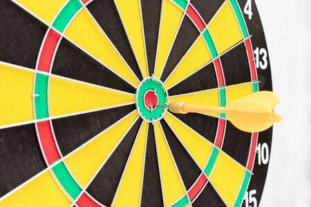 A dart board with an arrow in bullseye close up, goals and targetting concept. Reklamní fotografie - 141817257