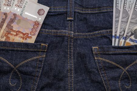 Russian rubles and us american dollar banknotes in different jeans pockets as a symbol of difficult choice between currences.