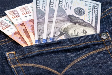 Russian rubles and us american dollars in a jeans pocket, choosing currency for saving money and wealth.