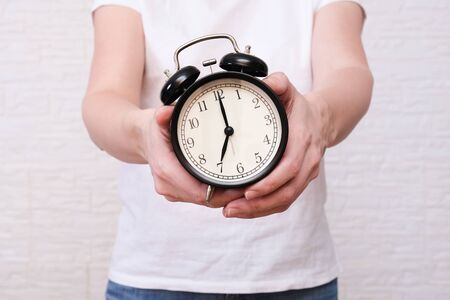 Woman holding an alarm clock in hands, the time is 7 am, early morning waking up.