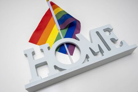 Lgbt rainbow gay pride flag and a sign home on white background. Reklamní fotografie