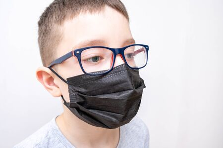 A portrait of a boy wearing surgical medical black face mask and glasses on white background. Reklamní fotografie