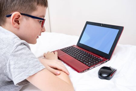 A boy wearing glasses lying in bed and using a laptop, typing the text on a keyboard close up, online education concept.