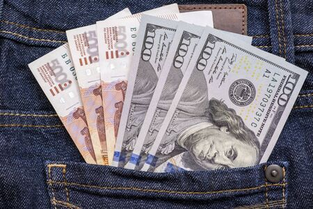 Russian rubles and us american dollars in a jeans pocket.