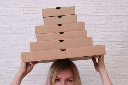 Young woman holding many stacked carton pizza boxes of different sizes on the head, restaurant to home delivery concept. Reklamní fotografie