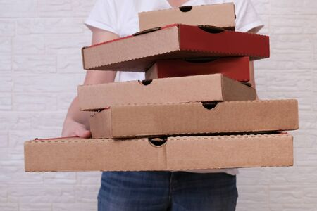 Woman holding many stacked in disorder carton pizza boxes of different sizes, restaurant delivery concept.