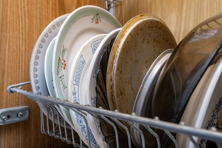 An unclean crockery, kitchen utensils, dishware of an elderle senior retired person with senile dementia.