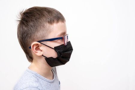 A portrait of a boy wearing surgical medical black face mask on white background, copy space.