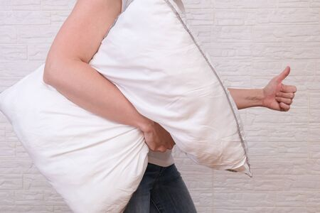 Woman holding white fluffy pillow in hands, hugging a pillow and showing thumb up - sleeping and resting concept. Reklamní fotografie