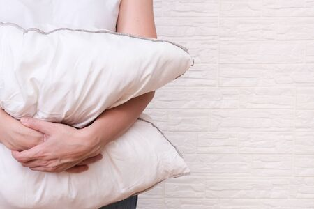 Woman holding white fluffy pillow in hands, hugging a pillow - sleeping and resting concept, copy space.