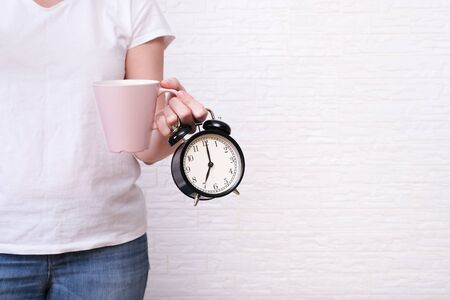 Woman holding a cup of coffee and alarm clock showing 7 am in hands, ready for work concept, copy space. Reklamní fotografie