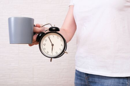 Woman in white t-shirt holding a big gray cup of coffee and alarm clock showing 7 am in hands, ready for work concept. Reklamní fotografie