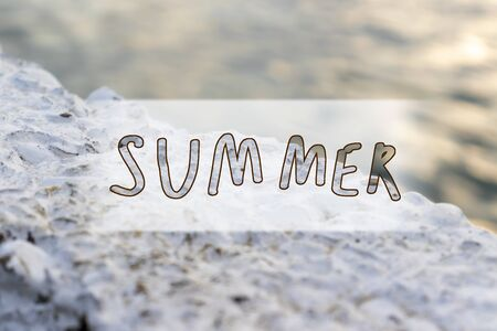 Handwritten sign summer on sunny sea background, travelling and vacation concept.