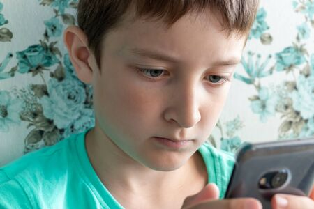 A teenage boy with serious face playing online games using smartphone.