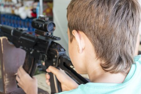 Caucasian teenage boy aiming with pneumatic rifle in shooting gallery, range.