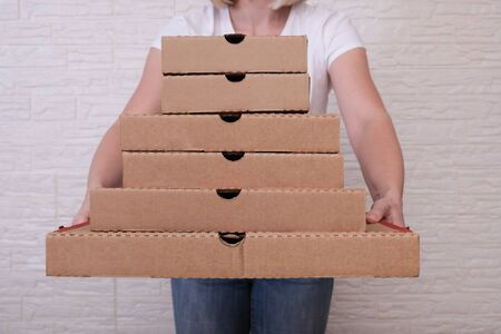 Woman holding many pizza boxes of different sizes.