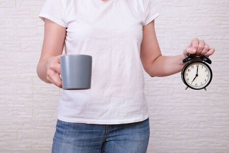 Woman holding a big gray cup of coffee and alarm clock showing 7 am in hands, ready for work with caffeine energy concept. 版權商用圖片