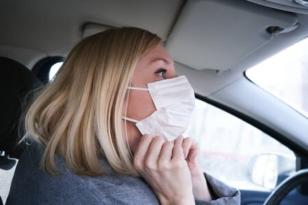 Caucasian european woman sitting in a car and putting on white surgical medical face mask as a way of protection against coronavirus