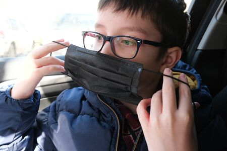 A teenage boy in car putting on surgical medical black face mask as a protection against virus disease, coronavirus prevention
