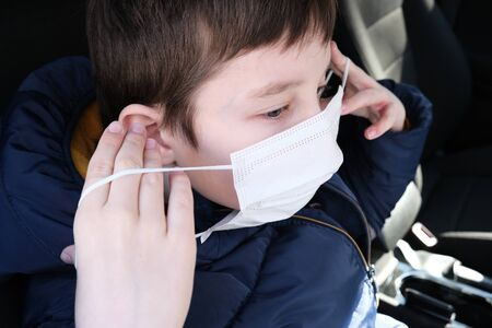 A european teenage boy in car putting on white protective surgical medical face mask as a protection against virus disease, coronavirus prevention