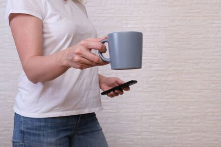 Business woman holding a big gray mug of coffee and using a smartphone in the morning. Reklamní fotografie