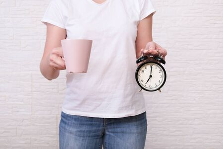 Woman holding a cup of coffee and alarm clock showing 7 am in hands, ready for work concept.