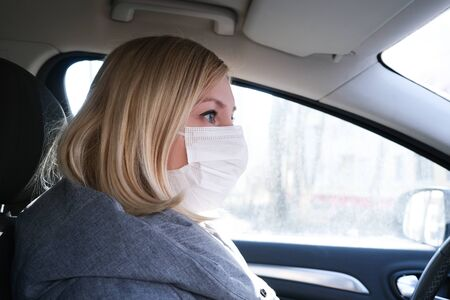 Caucasian european woman sitting in a car and putting on white surgical medical face mask as a way of protection against coronavirus and flu.