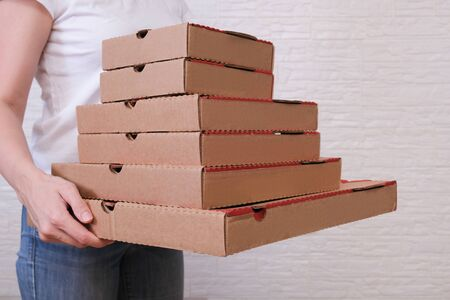 Woman holding many carton pizza boxes of different sizes, restaurant delivery concept.