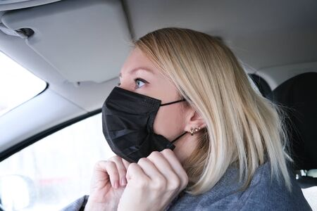 Caucasian european woman sitting in a car and putting on black surgical medical face mask as a way of protection against coronavirus.