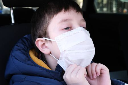 A teenage boy in car putting on white protective surgical medical face mask as a protection against virus disease, coronavirus prevention.
