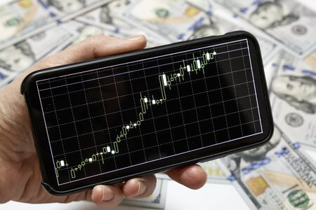 A stock forex exchange rate of us dollar on a smartphone screen, banknotes on background.