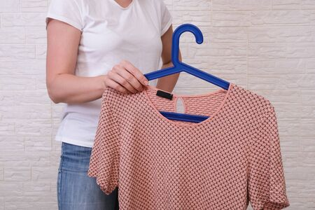 Caucasian woman choosing clothes, she is holding a hanger with beige t-shirt , shopping, fitting and buying clothes during sale and discount concept, cheap second hand clothes for online selling. Reklamní fotografie