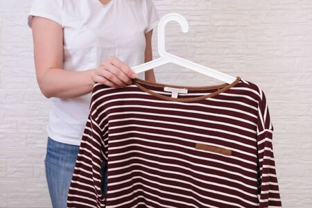 Caucasian woman choosing clothes, she is holding a hanger with striped sweatshirt , shopping, fitting and buying clothes during sale and discount concept, cheap second hand clothes for online selling Reklamní fotografie