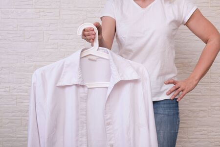 Caucasian woman choosing clothes, she is holding a hanger with white shirt, shopping, fitting and buying clothes during sale and discount concept, cheap second hand clothes for online selling.