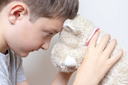 Concept of a child become a teen, teenager. A thoughtful grow up boy holding a soft toy, teddy bear, he is little old for playing toys. Stock Photo